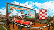 A junior rollercoaster speeds by a billboard for The Barnstormer featuring the Great Goofini