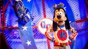Goofy, as the Great Goofini, stands next to his crashed motorcycle in a caged motordrome