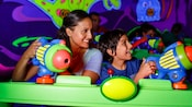 A mother and son aim space cannons during Buzz Lightyear's Space Ranger Spin