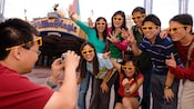 A dad takes a picture of family members wearing 3D glasses outside Mickey's PhilharMagic