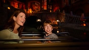 A mom and son look around while riding on the Pirates of the Caribbean attraction