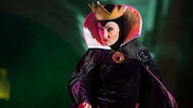 The scowling Evil Queen from Snow White and the 7 Dwarfs wears a crown and a cape clasped with a jeweled broach