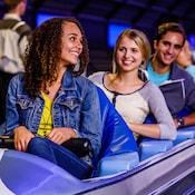 Des visiteurs assis dans un train en forme de fusée, prêts à commencer leur aventure à bord du Space Mountain, à Tomorrowland