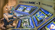 A one-eyed robot pushes buttons on several video screens at Tomorrowland Station M K 1 Command Center