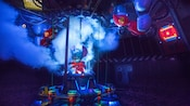 Smoke surrounds Stitch as he emerges from a transportation tube at Stitch's Great Escape! attraction