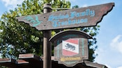 A wooden sign for Swiss Family Treehouse above another sign with the Robinson family crest