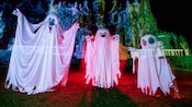 Translucent ghosts on a lawn of the Haunted Mansion after dark