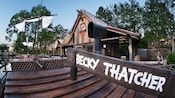 A raft named Becky Thatcher docked at the wooden loading area at the Tom Sawyer Island attraction