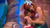 Ariel and a girl hug each other at Under the Sea ~ Journey of The Little Mermaid