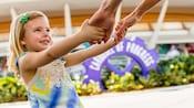 A little girl grabs her mother's hands and pulls her toward Walt Disney's Carousel of Progress