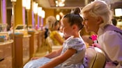 A Fairy Godmother-in-training looks over the shoulder of a girl she's transformed into a princess