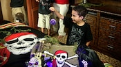 A boy plays with pirate gear on a bed inside a Pirate Room at Disney's Caribbean Beach Resort