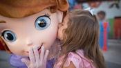 Una niña le da un beso en la mejilla a la Princesa Sofía de Disney, en Walt Disney World Resort