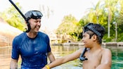 A father and a son wearing snorkels and masks smile at each other as they stand up in chest high water
