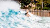 A female surfer rides a large wave at Disney's Typhoon Lagoon Surf Pool