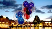 Three Mickey balloons float against the night sky while reflecting lights from Disney's Boardwalk Inn
