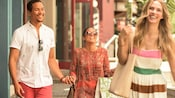 Two smiling women and a man stroll the promenade together