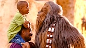 Little boy sitting on his father's shoulders meets Star Wars character Chewbacca