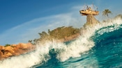 A wave crashes at Typhoon Lagoon Surf Pool with the water park's iconic shipwreck in the background