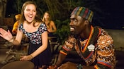 A girl plays a conga drum next to a guide who is wearing a colorful dashiki