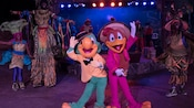 Jose and Panchito from The Three Caballeros dance with dancers and stilt walkers as a band plays