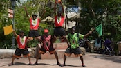 Five members of the Harambe Soccer Meerkats, wearing African style shirts and shorts, pose playfully in a pyramid formation