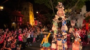 In a market square setting at night, the Harambe Village Acrobats perform in African style costumes as a large audience looks on, applauding and cheering