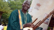 The street musician Kora Tinga Tinga strolls through Harambe Village playing the kora, a traditional African harp