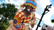 The street entertainer Muziki, smiling broadly, wears a flamboyant African inspired costume as he entertains Guests in Harambe Village