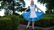 Alice holds her dress to curtsy at Meet a Wonderful Friend in the United Kingdom at Epcot