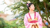 Mulan wears a colorful Chinese robe and flowers in her hair as she gazes into the distance