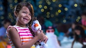 A little girl smiles while holding her Olaf plush toy
