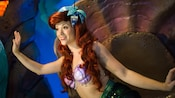 Ariel smiles and waves in an aquatic cave