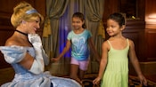 Two little girls curtsy to a smiling Cinderella at Princess Fairytale Hall in Fantasyland