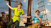 Peter Pan holds Wendy's hand while standing on the deck of a pirate ship