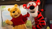 Winnie the Pooh and Tigger strike a pose near the Many Adventures of Winnie the Pooh