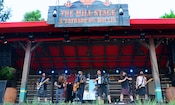 6 male musicians wearing a mixture of kilts and grunge attire perform on The Mill Stage with electric and acoustic guitars, an accordion, a fiddle and a flute