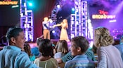 Una familia sonríe mientras mira la serie de conciertos Disney on Broadway