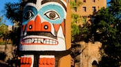 An ornately painted tribal face on a totem pole, located outdoors at the Canada Pavilion at Epcot