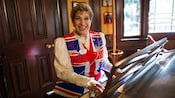 A female pub musician sits at a piano and wears a British flag-inspired vest