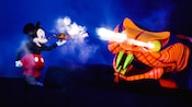 Mickey Mouse holds a genie's lamp up to a giant cobra in Fantasmic!