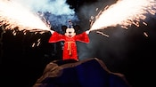 Fireworks shoot from the hands of Sorcerer Mickey Mouse in Fantasmic!