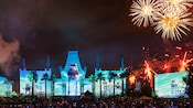 A crowd looks on as fireworks burst above a replica of Grauman's Chinese Theatre at Disney's Hollywood Studios