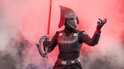 The Seventh Sister Inquisitor holds her lightsaber and stands in front of a wall of smoke