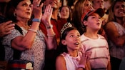 In the audience of The Music of Pixar Live, a young girl wearing a princess crown claps to the music while a young boy wearing a baseball cap looks to the stage