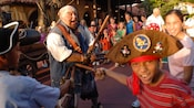 Young pirate gesturing with a wood club at Mack during Captain Jack Sparrow's Pirate Tutorial