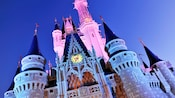 The top spires of Cinderella Castle bathed in pink light, as part of 'Celebrate the Magic' nighttime projection show