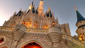 Cinderella Castle towering into the Florida sky as its windows glimmer under the light of a sunset