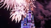 Fireworks erupting above Cinderella Castle decorated in icicles and colored lights