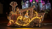 Goofy riding aboard a locomotive as it cascades with vibrant lights in front of Cinderella Castle